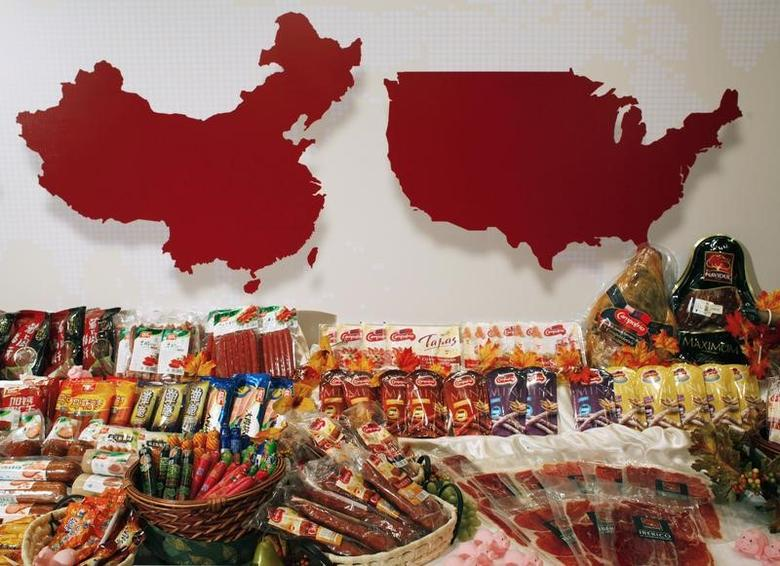 File Photo: Some of the products of WH Group are displayed in front of maps of China (L) and  the United States at a news conference on the company's IPO in Hong Kong April 14, 2014.   REUTERS/Bobby Yip