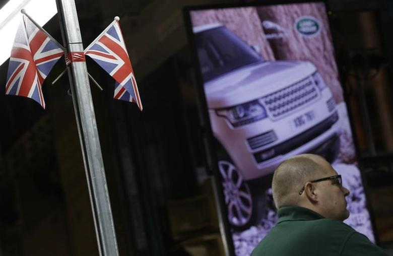 A worker stands under Union Flags  at the Jaguar Land Rover facility in Solihull, Britain, January 30, 2017. REUTERS/Darren Staples