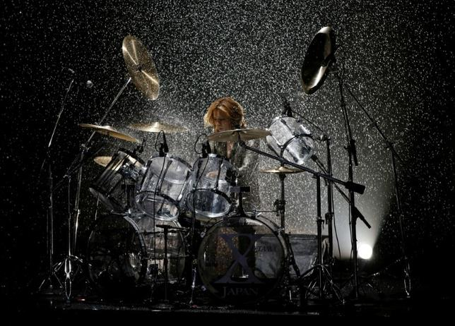 Designer Yoshiki, leader of Japan's band ''X Japan,'' plays drums during his Spring/Summer 2017 collection show for his brand YOSHIKIMONO at Tokyo Fashion Week in Tokyo, Japan October 17, 2016. REUTERS/Toru Hanai/Files