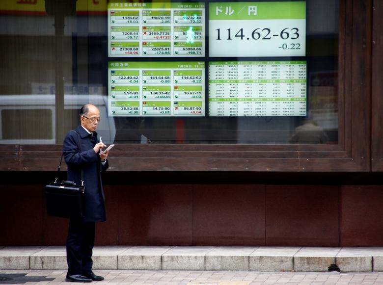 A man stands in front of electronic boards showing stock prices and exchange rate between Japanese Yen and U.S dollar outside a brokerage in Tokyo, Japan, January 20, 2017.  REUTERS/Kim Kyung-Hoon