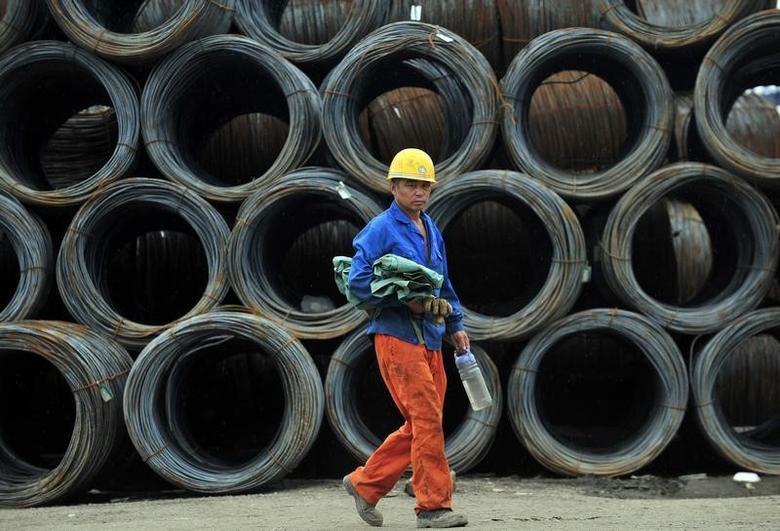 2013年7月,辽宁沈阳一处钢材批发市场,一名工人路过待售的大量钢筋。REUTERS/Stringer