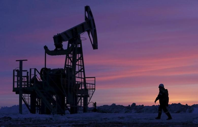 FILE PHOTO:  A worker walks past a pump jack on an oil field owned by Bashneft in Bashkortostan, Russia, January 28, 2015.      REUTERS/Sergei Karpukhin/File Photo