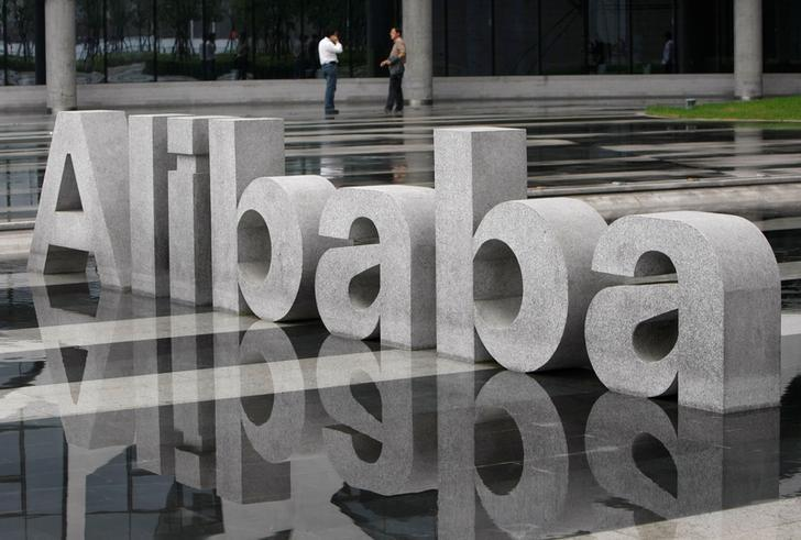 Two men chat beside a logo of Alibaba (China) Technology Co. Ltd at its headquarters on the outskirts of Hangzhou, Zhejiang province May 17, 2010.  REUTERS/Steven Shi/File Photo