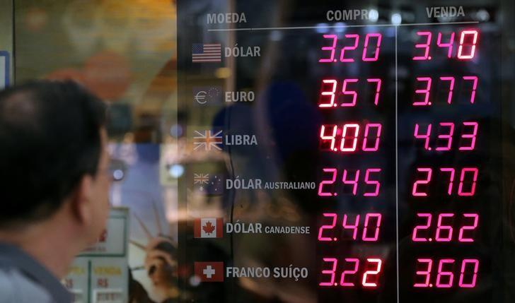 A man observes a board showing the Brazilian Real-U.S. dollar and several other foreign currencies exchange rates in Rio de Janeiro, Brazil November 9, 2016. REUTERS/Sergio Moraes