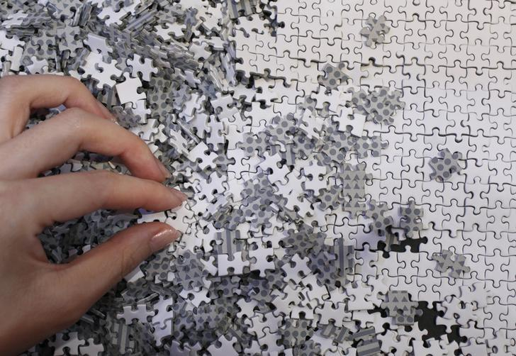 An employee of puzzle maker Beverly holds a piece of the company's white micro 1000 piece jigsaw puzzle at the International Toy Show in Tokyo June 14, 2012.