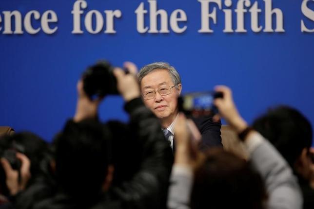 3月10日、中国人民銀行(中央銀行)の周小川総裁は、中国企業の債務水準は過度に高いとの認識を示し、銀行はレバレッジの高い企業を支えることはできないと述べた。写真は全国人民代表大会(全人代)の合間に開いた記者会見に出席する同総裁。北京で撮影(2017年 ロイター/Jason Lee)