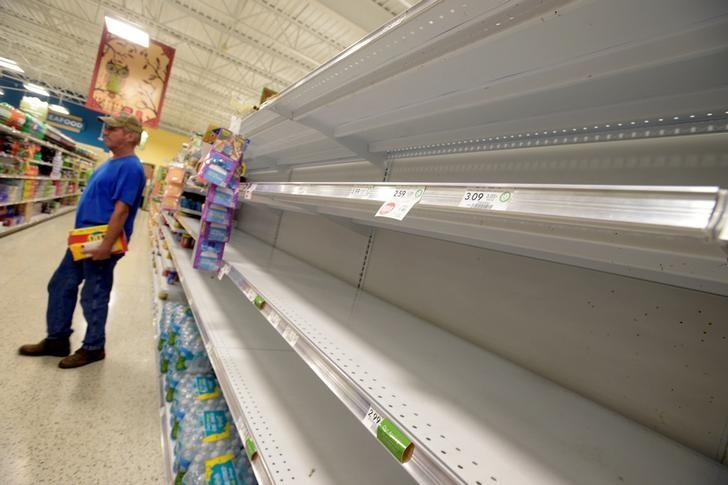 Shelves that held water bottles sit empty at a supermarket before the arrival of Hurricane Matthew in South Daytona, Florida, U.S., October 6, 2016. REUTERS/Phelan Ebenhack/File Photo