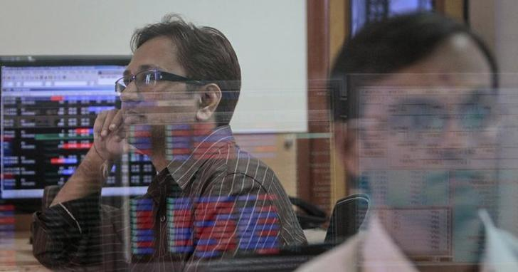 A broker (L) watches a TV news channel as another monitors share prices at a brokerage firm in Mumbai August 9, 2011. REUTERS/Danish Siddiqui/File Photo