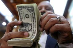 Мужчина пересчитывает долларовые купюры в пункте обмена валюты в Каире 7 марта 2017 года. Доллар укрепился до шестинедельного максимума к иене в пятницу, приготовившись завершить неделю ростом к основным валютам. REUTERS/Mohamed Abd El Ghany