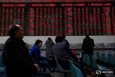 Инвесторы в брокерской конторе в Шанхае 3 января 2017 года. Акции Китая завершили торги пятницы без изменений, так как ежегодное заседание парламента страны не преподнесло сюрпризов, а инвесторы начали проявлять осторожность в преддверии вероятного повышения ставки в США на следующей неделе. REUTERS/Aly Song