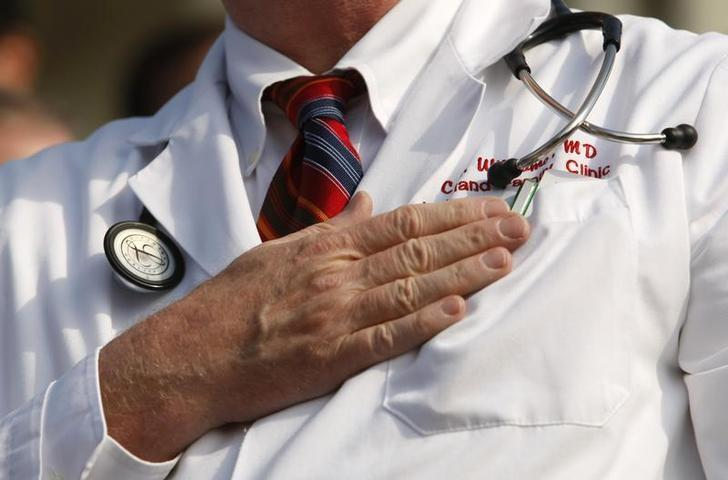 A doctor puts his hand over his chest during a ''House call'' rally against proposed healthcare reform legislation at the Capitol in Washington November 5, 2009.    REUTERS/Kevin Lamarque/Files