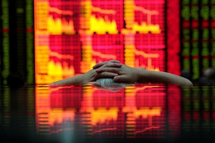 FILE PHOTO -  A man looks at an electronic board at a brokerage house in Shanghai August 31, 2009.  REUTERS/Aly Song/File Photo