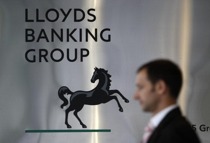 A pedestrian is seen passing the head office of the Lloyds Banking Group in central London in this August 5, 2009 file photograph. Britain has launched the sale of its shares in Lloyds Banking Group, a milestone in the country's recovery from the 2008 financial crisis, a Treasury statement announced on September 16, 2013. REUTERS/Stefan Wermuth/File Photo