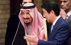 Le Premier ministre japonais Shinzo Abe (à droite) a demandé lundi au roi Salman d'Arabie saoudite (à gauche) d'appuyer la candidature de la Bourse de Tokyo pour accueillir la cotation de Saudi Aramco, le géant saoudien du pétrole et du gaz qui prépare son entrée en Bourse l'an prochain. /Photo prise le 13 mars 2017/REUTERS/Tomohiro Ohsumi
