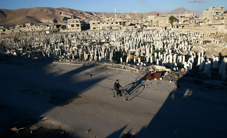A civilian rides a bicycle past a cemetery in the rebel held besieged Douma neighbourhood of Damascus, Syria January 3, 2017. REUTERS/Bassam Khabieh