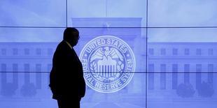 Охранник у экрана с изображением логотипа ФРС в Вашингтоне 16 марта 2016 года. Турецкие банки, украинский агрохолдинг, пребывающие в кризисе страны, такие как Нигерия и Египет, торопятся занять деньги на рынке долларовых облигаций в этом году, пытаясь успеть перед ожидаемым аналитиками решением ФРС США о повышении ставки. REUTERS/Kevin Lamarque/File Photo