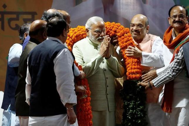 3月14日、インド株式市場で、指標となるNSE指数が一時2.1%値上がりし、過去最高値を更新した。写真は与党インド人民党(BJP)本部での式典で花輪をかけられるモディ・インド首相。ニューデリーで12日撮影(2017年 ロイター/Adnan Abidi)