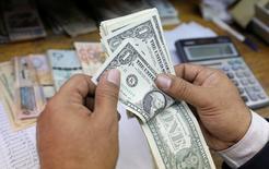 Мужчина пересчитывает долларовые купюры в обменном пункте в Каире 7 марта 2017 года. Доллар немного вырос к корзине основных валют во вторник, в то время как доходность госбондов США усилила рост в преддверии ожидаемого повышения ставок Федрезервом. REUTERS/Mohamed Abd El Ghany