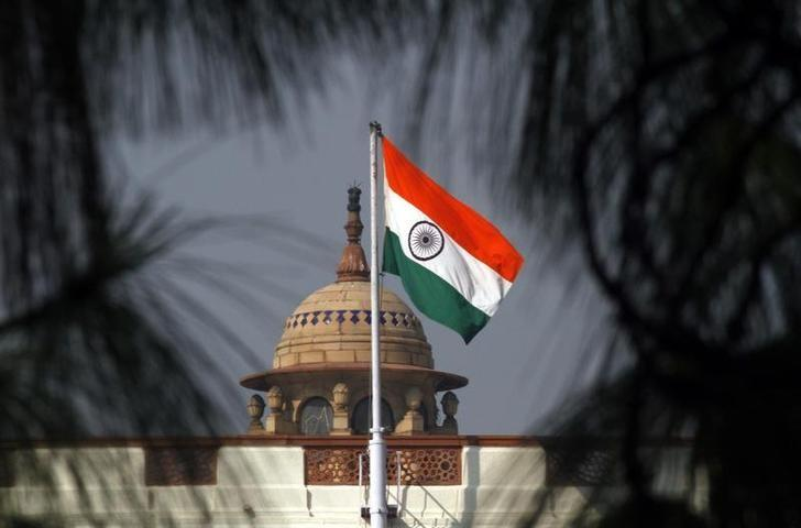 An Indian national flag flutters on top of the parliament building in New Delhi December 1, 2010. REUTERS/B Mathur/Files