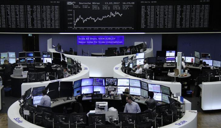 Traders work at their desks in front of the German share price index, DAX board, at the stock exchange in Frankfurt, Germany, March 13, 2017. REUTERS/Staff/Remote