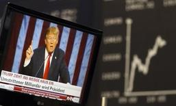 Экран с изображением Дональда Трампа на фондовой бирже во Франкфурте-на-Майне. 9 ноября 2016 года. Одной из главных загадок со стороны мировых рынков сегодня, в эру Трампа, является исторически низкий уровень их волатильности, несмотря на все пертурбации и неопределенность, которые может принести его президентство. REUTERS/Staff/Remote