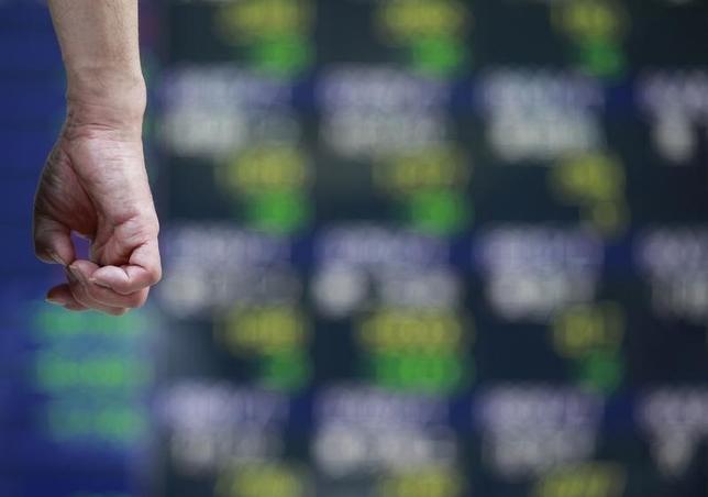 3月15日、東京株式市場で日経平均は、続落となった。米国株安や原油先物の続落を受け幅広い銘柄に売りが先行、一時100円を超える下げ幅となった。米連邦公開市場委員会(FOMC)やオランダ下院選など重要イベントを控え、投資家のリスク回避姿勢が強まった。写真は都内の株価ボードに見入る通行人。2012年9月撮影(2017年 ロイター/Yuriko Nakao)