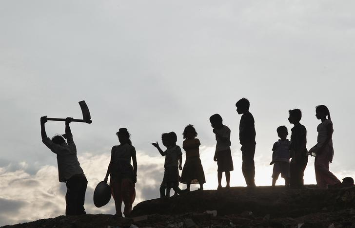Children stand next to a labourer working on the banks of river Ganges as they are silhouetted against the setting sun in Allahabad July 3, 2013. REUTERS/Jitendra Prakash/Files