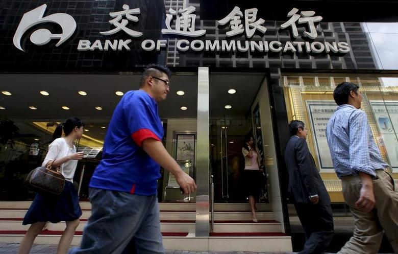 FILE PHOTO: People walk past the Bank of Communications at its central branch in the financial district of Hong Kong August 19, 2009. REUTERS/Aaron Tam/File Photo