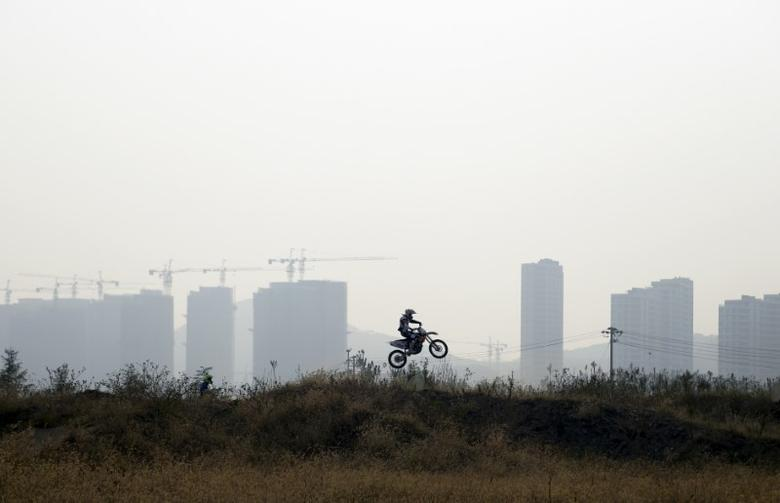 A motorcyclist practices near buildings in construction in Qingdao, Shandong province, China October 20, 2015. REUTERS/Stringer