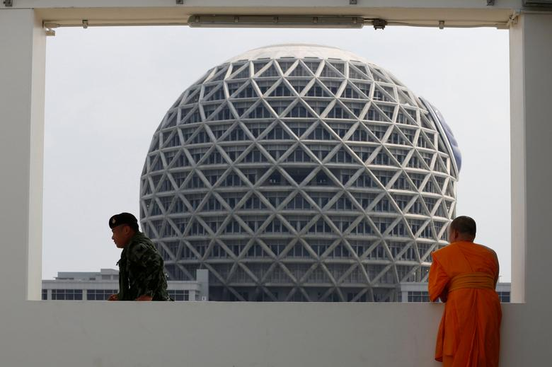 A soldier walks next to a Buddhist monk during an inspection of the Wat Phra Dhammakaya temple, in Pathum Thani province, Thailand March 10, 2017. REUTERS/Chaiwat Subprasom