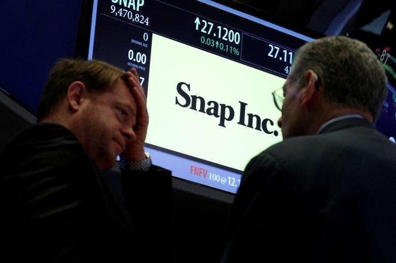 Traders gather at the post where Snap Inc. is traded on the floor of the New York Stock Exchange (NYSE) in New York, U.S., March 6, 2017. REUTERS/Brendan McDermid