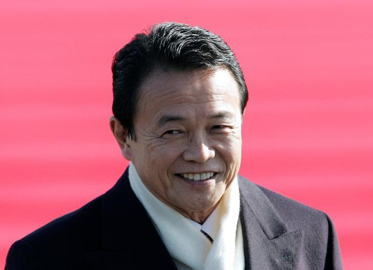 Japan's Prime Minister Taro Aso smiles upon his arrival at a military airport in Seongnam, near Seoul, January 11, 2009.   REUTERS/Jo Yong-Hak/Files