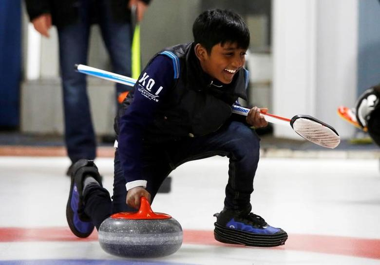 A refugee from Sri Lanka, Arun Daniel, learns the sport of curling at the Royal Canadian Curling Club during an event put on by the ''Together Project'', in Toronto, March 15, 2017.    REUTERS/Mark Blinch -