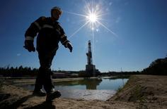 Буровая вышка на нефтяном месторождении у Нефтеюганска. Цены на нефть сохраняют положительную динамику на вечерних торгах четверга благодаря ослаблению доллара и снижению запасов сырья в США.   REUTERS/Sergei Karpukhin