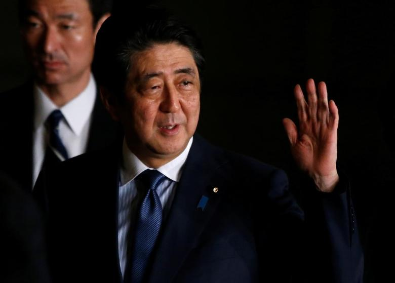 Japan's Prime Minister Shinzo Abe raises his hand as he walks at his official residence in Tokyo, Japan March 16, 2017.   REUTERS/Toru Hanai