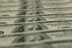 Долларовые купюры в банке OTP в Будапеште 23 ноября 2011 года. Доллар пытался восстановить потери на азиатских торгах пятницы, удерживаясь вблизи минимумов пяти недель к корзине основных валют и готовясь завершить неделю в минусе после того, как Федрезерв сигнализировал о меньшем, чем ждали некоторые инвесторы, количестве повышений ставок в этом году. REUTERS/Laszlo Balogh