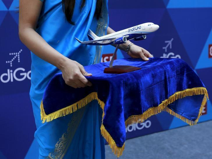 A woman holds a Indigo memento during the company's listing ceremony at the National Stock Exchange (NSE) in Mumbai, India, November 10, 2015. REUTERS/Danish Siddiqui/File Photo