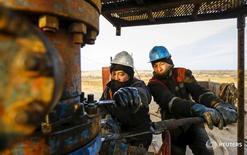 Рабочие на нефтяном месторождении РД Казмунайгаз в Кызылординской области Казахстана 21 января 2016 года. Казахстан, зависящий от мировой цены на сырье, ждет роста активов Национального фонда до $80 миллиардов к 2030 году при мировой цене на нефть в $50 за баррель, хочет ограничить займы правительства и квазигосударственного сектора объемом валютных активов Нацфонда, сказал министр экономики Тимур Сулейменов, выступая в верхней палате парламента. REUTERS/Shamil Zhumatov