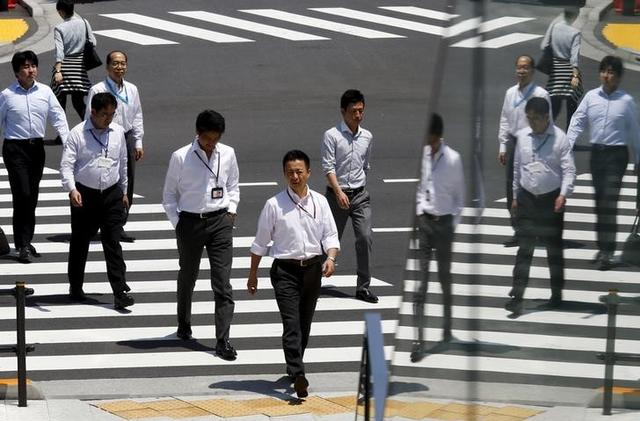 Office workers are reflected in a glass railing as they cross a street during lunch hour in Tokyo June 1, 2015. Japanese manufacturing activity expanded in May for the first time in two months as domestic orders and output rose, suggesting the economy may be grinding higher again after faltering in April.  REUTERS/Thomas Peter      TPX IMAGES OF THE DAY