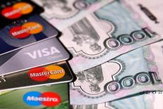 Пластиковые карты и рублевые купюры. Постепенное восстановление темпов прироста потребительского кредитования в среднесрочной перспективе не будет препятствовать достижению Банком России цели по инфляции в конце 2017 года, говорится в финансовом обозрении регулятора.  REUTERS/Maxim Zmeyev/Illustration