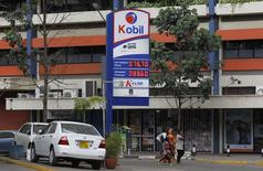 Pedestrians walk past a Kobil service station with the prices display of petrol (US $ 0.84 per litre unleaded) and diesel (US $ 0.72 per litre) on a signage in Kenya's capital Nairobi, February 7, 2016. The global oil price is hovering at about $30 U.S. dollars a barrel. REUTERS/Thomas Mukoya