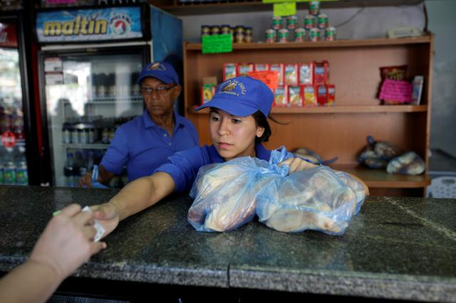 A saleswoman sells bread at a bakery in Caracas, Venezuela March 17, 2017. REUTERS/Marco Bello