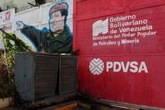Логотип PDVSA рядом с граффити Уго Чавеса на АЗС в Каракасе. 2 марта 2017 года. Государственная нефтяная компания Венесуэлы PDVSA предложила российской Роснефти долю в совместном предприятии, занимающемся разработкой участка в бассейне реки Ориноко, богатом сверхтяжелой нефтью, сообщили пять источников в отрасли, что говорит о тяжелой экономической ситуации в Венесуэле и растущем влиянии России в стране. REUTERS/Carlos Garcia Rawlins