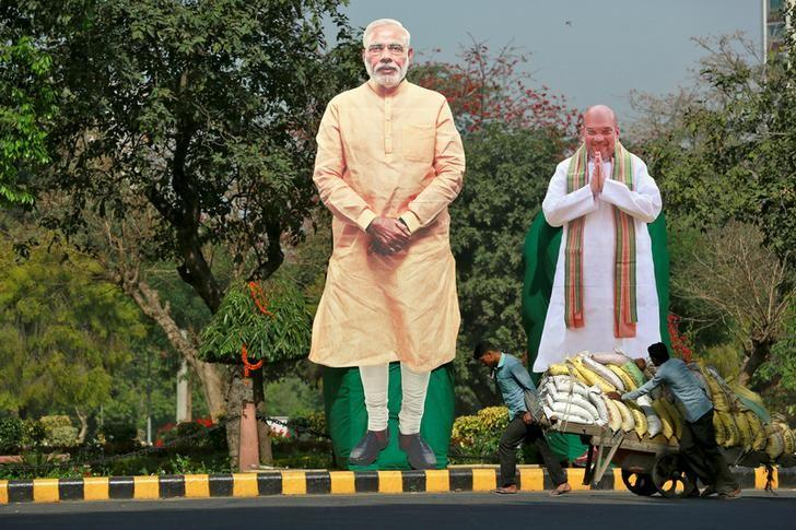 Giant cardboard cut outs of Indian Prime Minister Narendra Modi (C) and Bharatiya Janata Party president Amit Shah are displayed in New Delhi, India, March 15, 2017. REUTERS/Cathal McNaughton