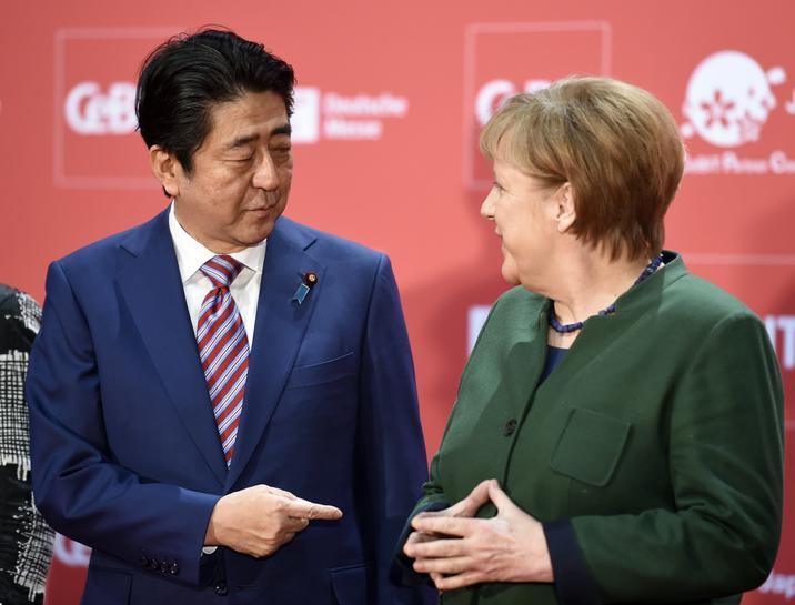 Germany's Merkel and Japan's Abe urge free trade with jabs at U.S.