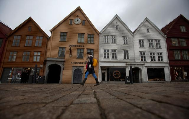 A woman walks near Bryggen (the Wharf) near the marina in downtown Bergen. REUTERS/Stoyan Nenov