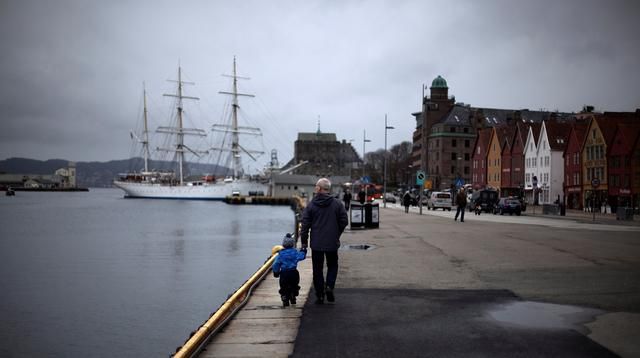 A man walks with a child near the marina in downtown Bergen, southwestern Norway.  REUTERS/Stoyan Nenov
