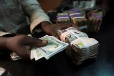 A trader changes dollars with naira at a currency exchange store in Lagos, Nigeria, February 12, 2015.  REUTERS/Joe Penney