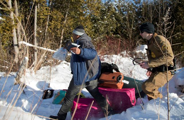 FILE PHOTO --  A man who claimed to be from Sudan runs for the border holding his family's passports as he is chased by a U.S. border patrol officer as he was detained after his family crossed the U.S.-Canada border into Hemmingford, Canada, from Champlain in New York, U.S., February 17, 2017.  REUTERS/Christinne Muschi/File Photo