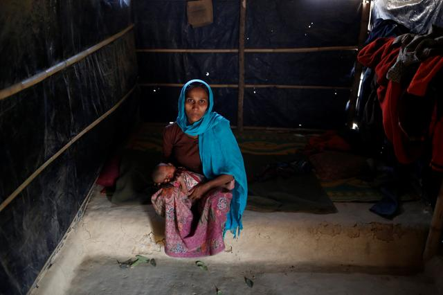 Ramida Begum, 35, holds her 10-day-old unnamed daughter as she poses for a photograph inside their shelter in Kutupalang unregistered refugee camp in Cox's Bazar, Bangladesh, February 10, 2017.  REUTERS/Mohammad Ponir Hossain